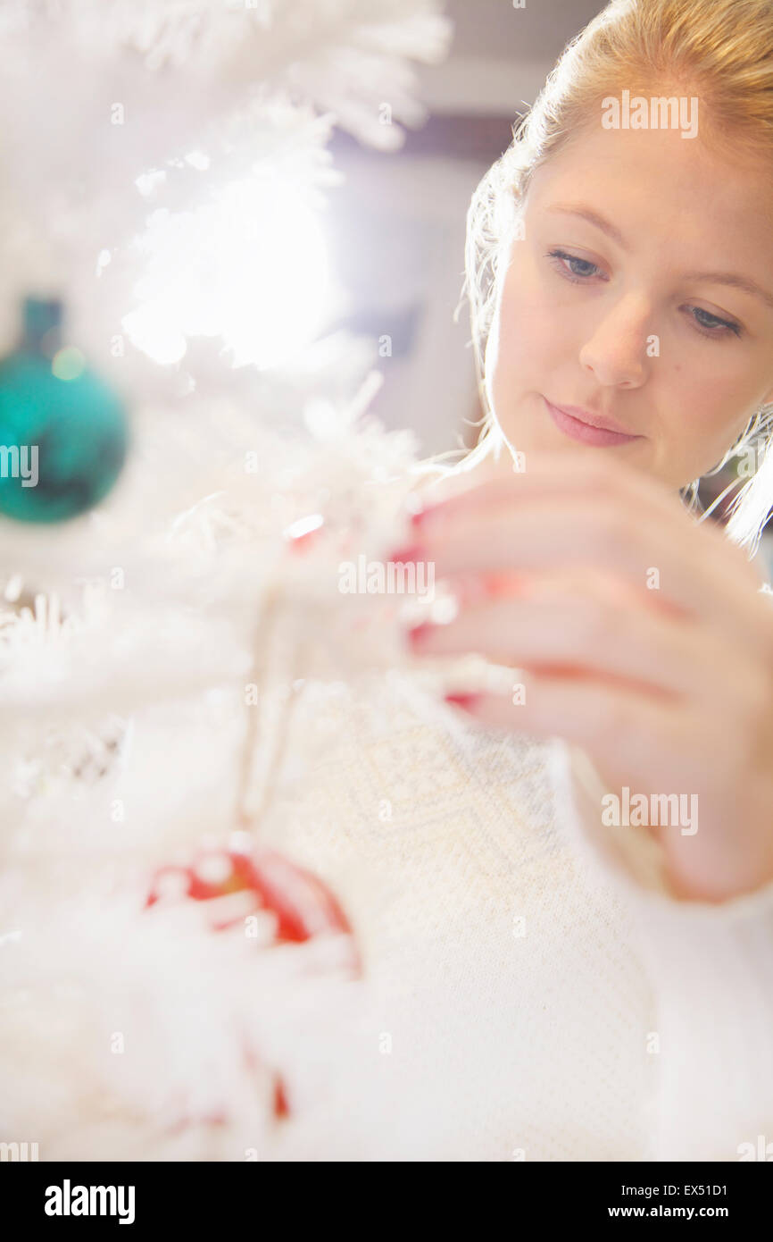 Close up of Young Woman Decorating Christmas Tree Stock Photo