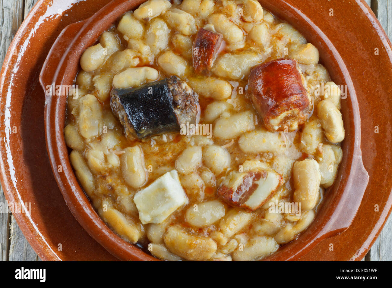 Spanish fabada in an earthenware dish and wooden background Stock Photo