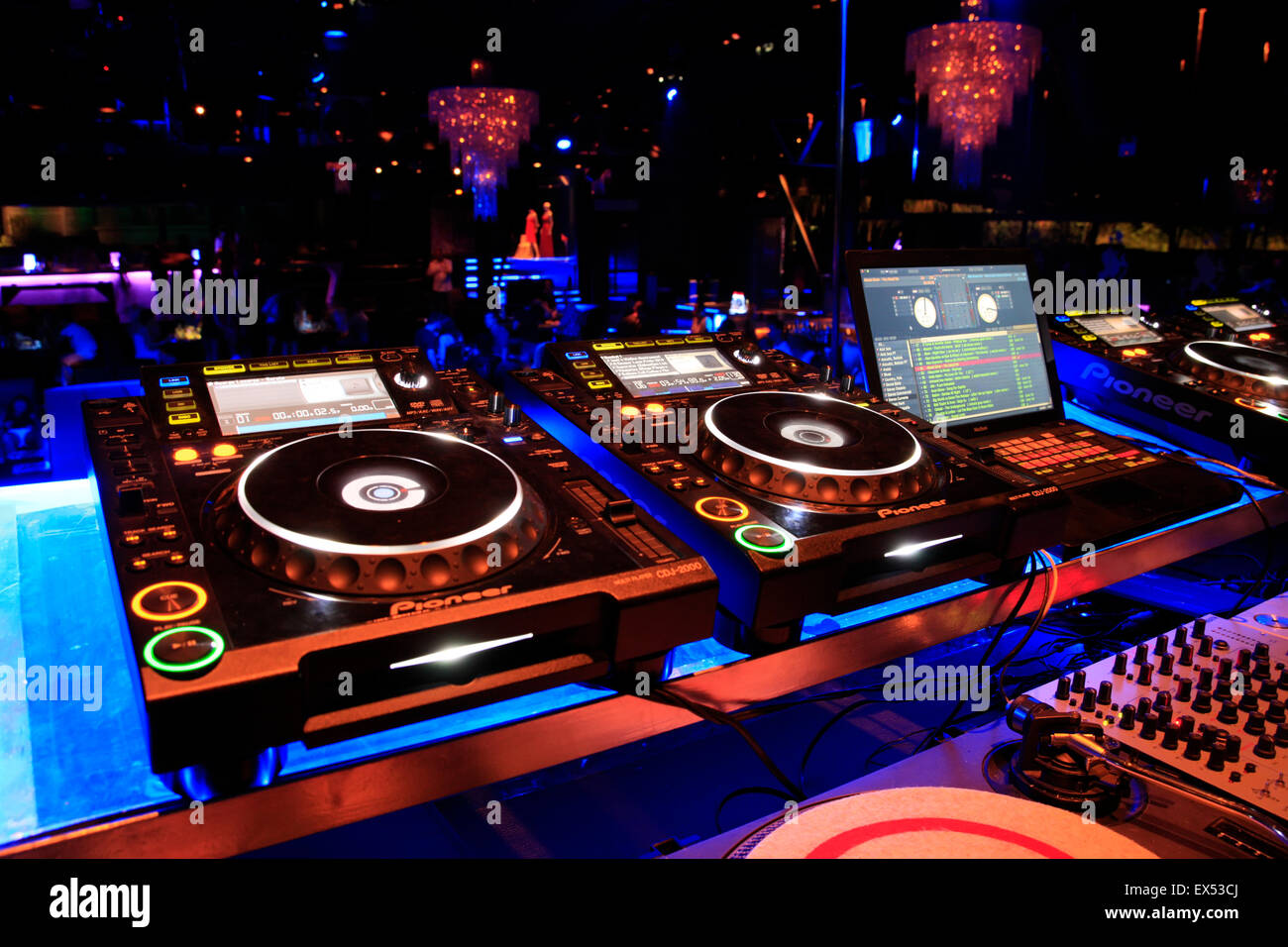 Image of audio mixing devices / decks and a laptop loaded with music software suite with glowing chandeliers in - Stock Image