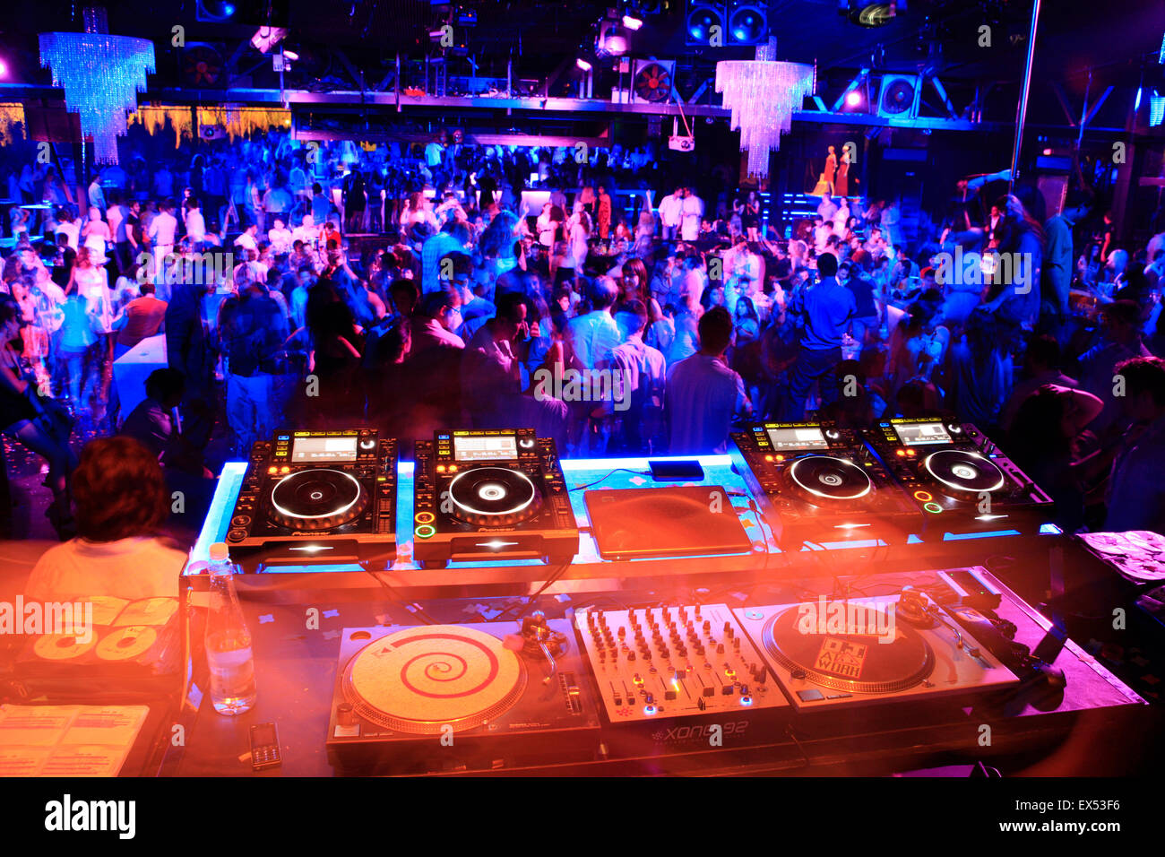 Colourful image of mixing console and decks playing music and jolified clubbers in the background. Athens nightclub, - Stock Image
