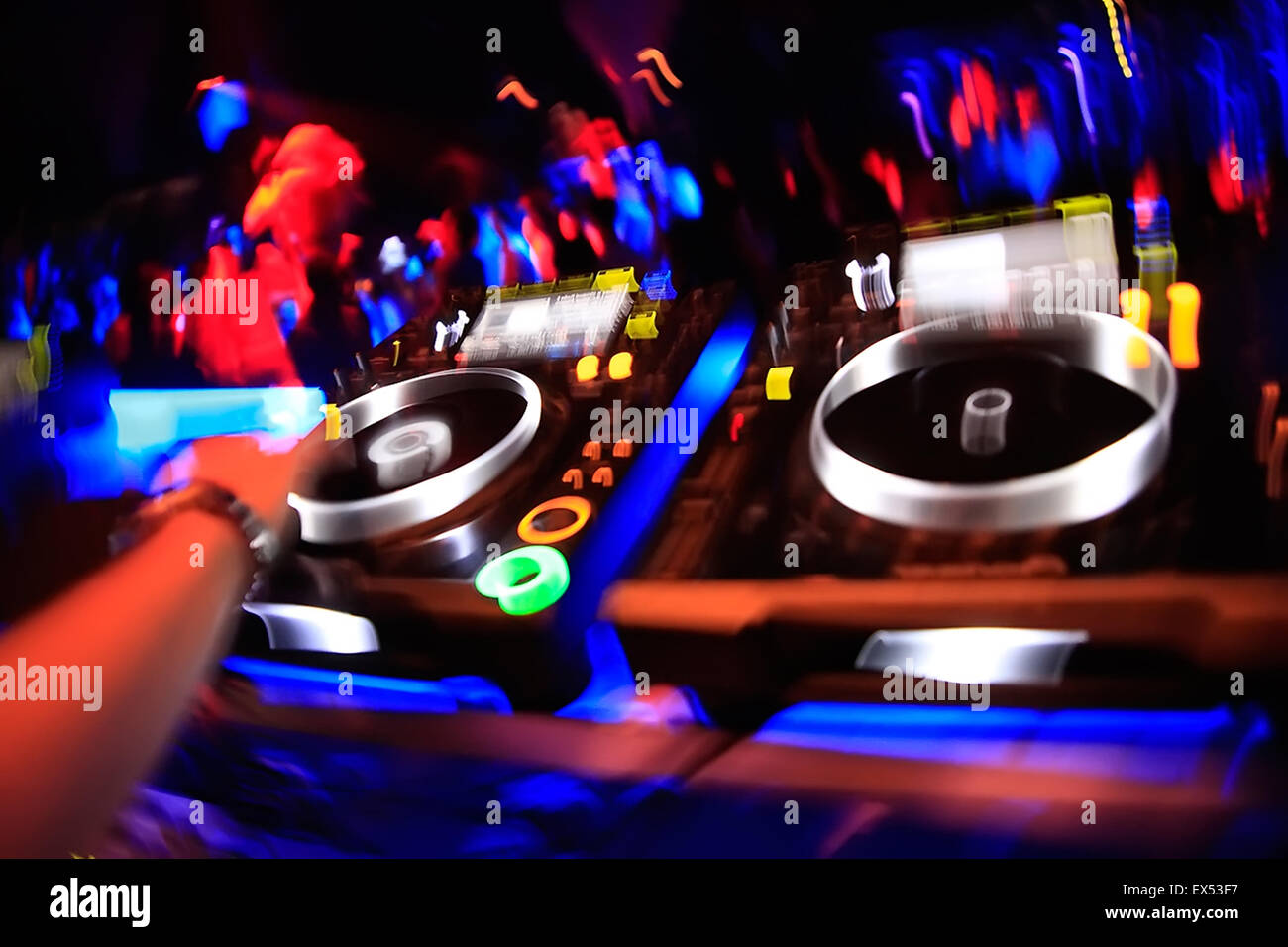 Colourful motion image of a DJ hand synchronising mysic on the decks / sound mixing devices. Athens nightclub, Greece. - Stock Image