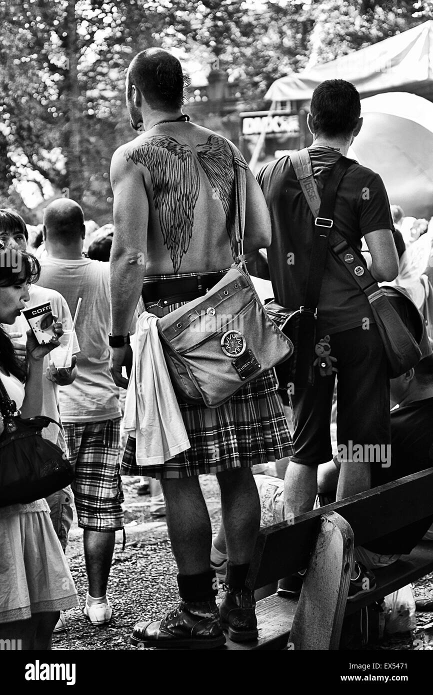 A man in his  kilt standing on a bench in the Forest on the Island in Prague. Prague pride 2013. - Stock Image