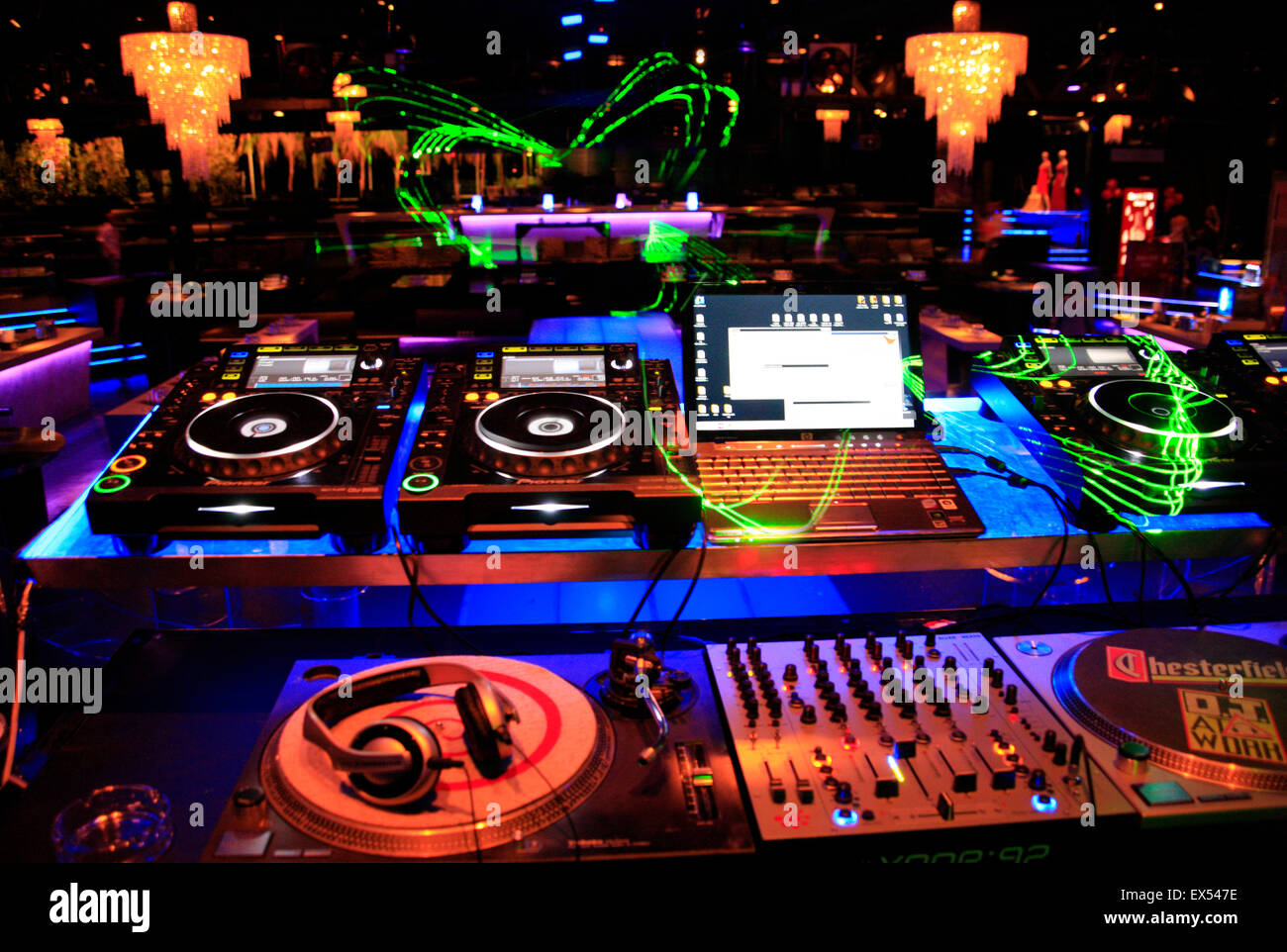 Music / sound mixing equipment decks, computers, laptops, and laser beam designs in a nightclub in Athens, Greece - Stock Image