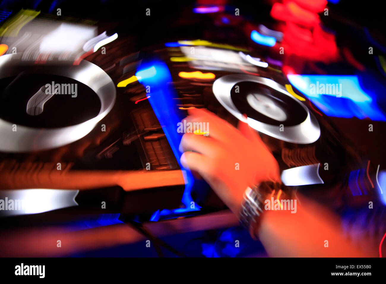 Colourful motion image of a DJ hand making mysic on the decks / sound mixing devices. Athens nightclub, Greece. - Stock Image