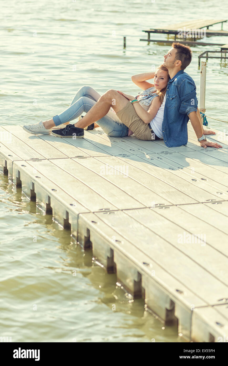 Couple in love sitting on the pier, embrace Stock Photo