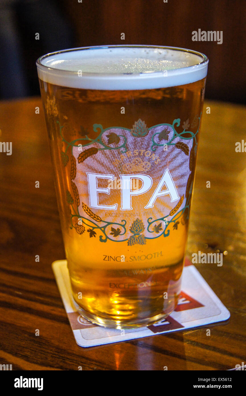 A pint of Marston's EPA real ale on a beermat pub table drinks glasses - Stock Image