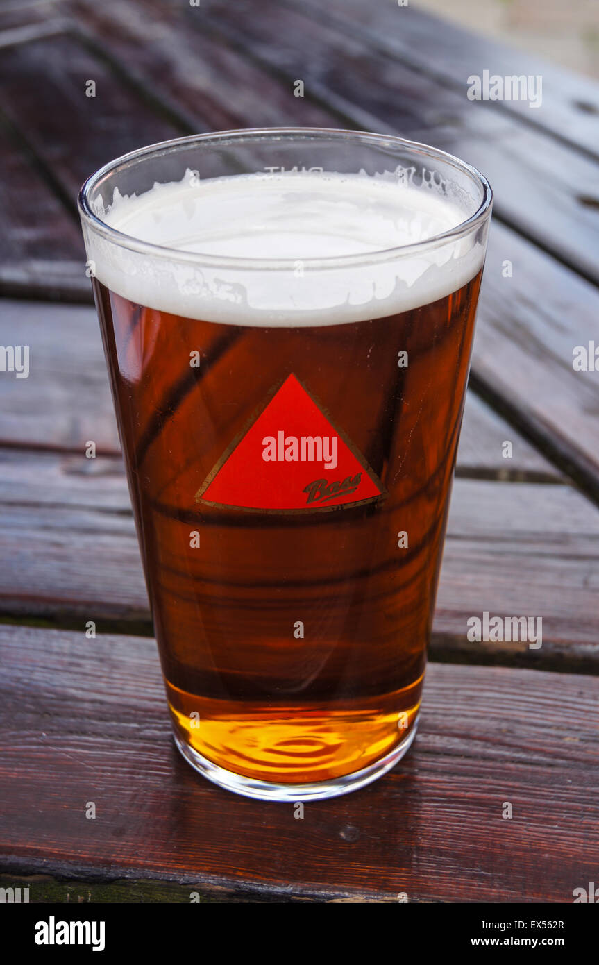 A pint of draught Bass real ale on a pub table pub table drinks glasses - Stock Image