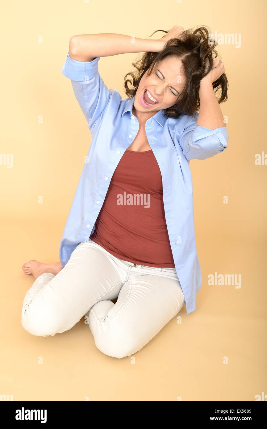 Attractive Young Woman Sitting on the Floor Wearing a Blue Shirt and White Jeans Having a Temper Tantrum Pulling - Stock Image