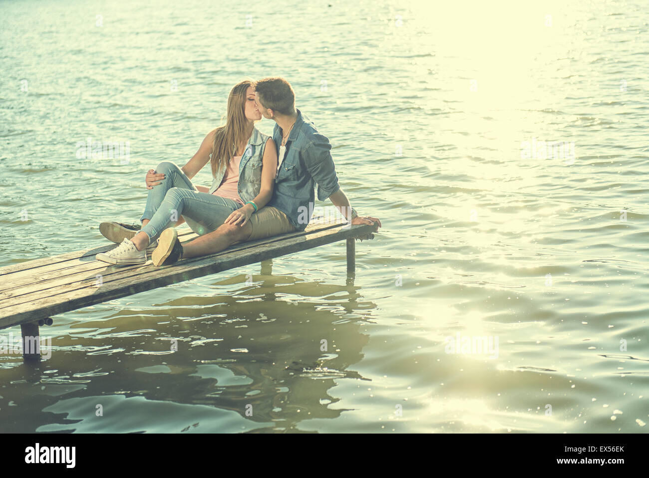 Couple in love sitting on the pier - Stock Image