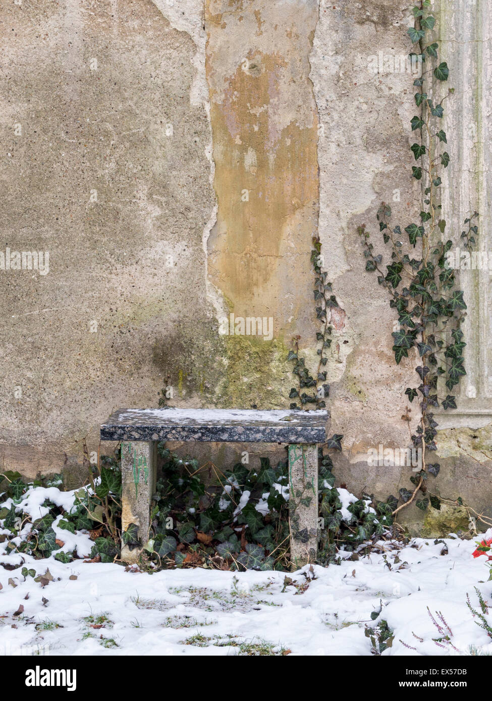 Stone bench, creeper and old cracked wall in winter - Friedhof der Sophien Gemeinde, Berlin cemetery. - Stock Image
