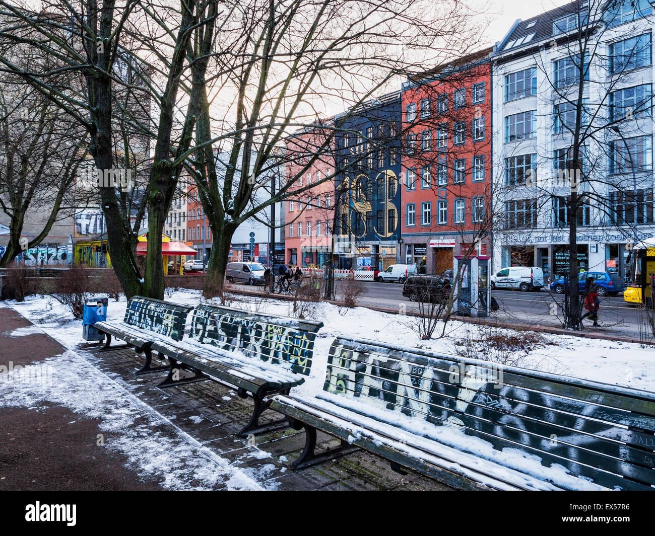 Berlin street and public park view covered with snow in Winter. Road lined with newly renovated apartment buildings - Stock Image