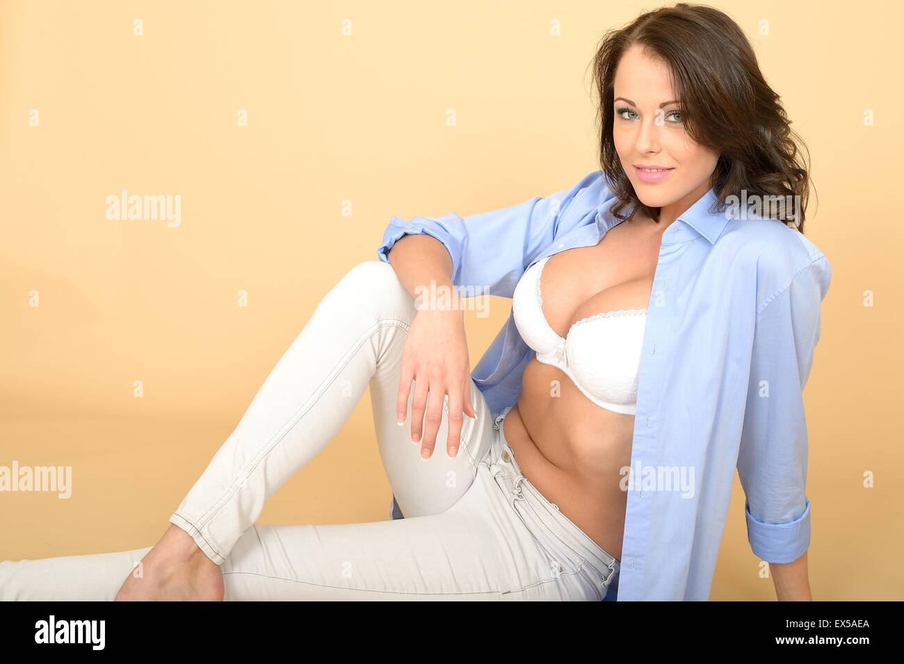 9cac4841e37 Attractive Beautiful Sexy Sensual Young Woman Sitting on the Floor Wearing  a Blue Shirt and White Jeans and Bra Lingerie