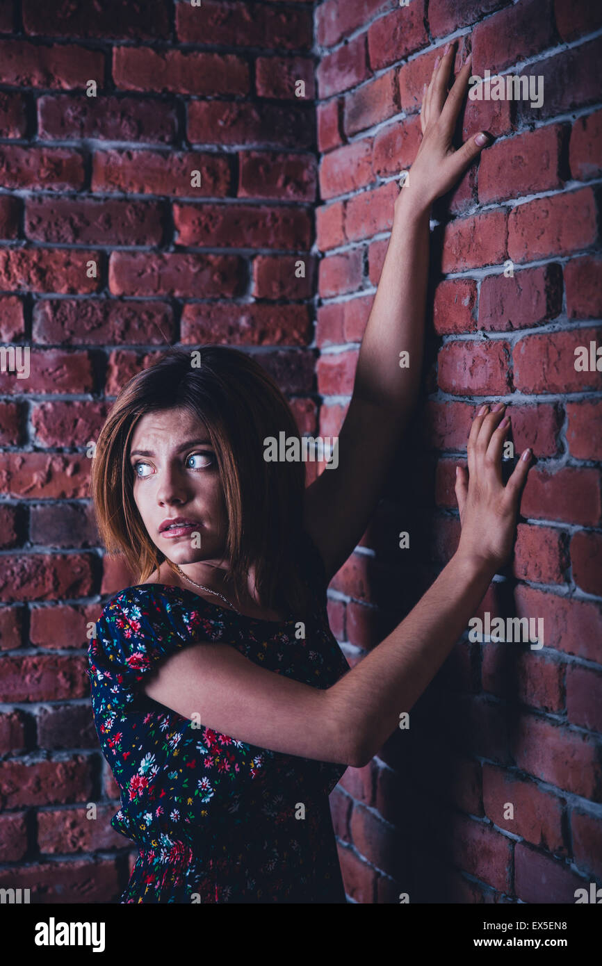 Scared young woman standing in corner of brick wall and looking away Stock Photo