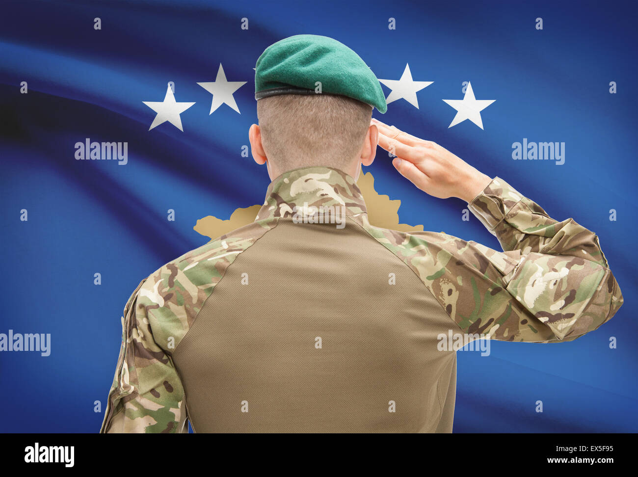 Soldier in hat facing national flag series - Kosovo Stock Photo