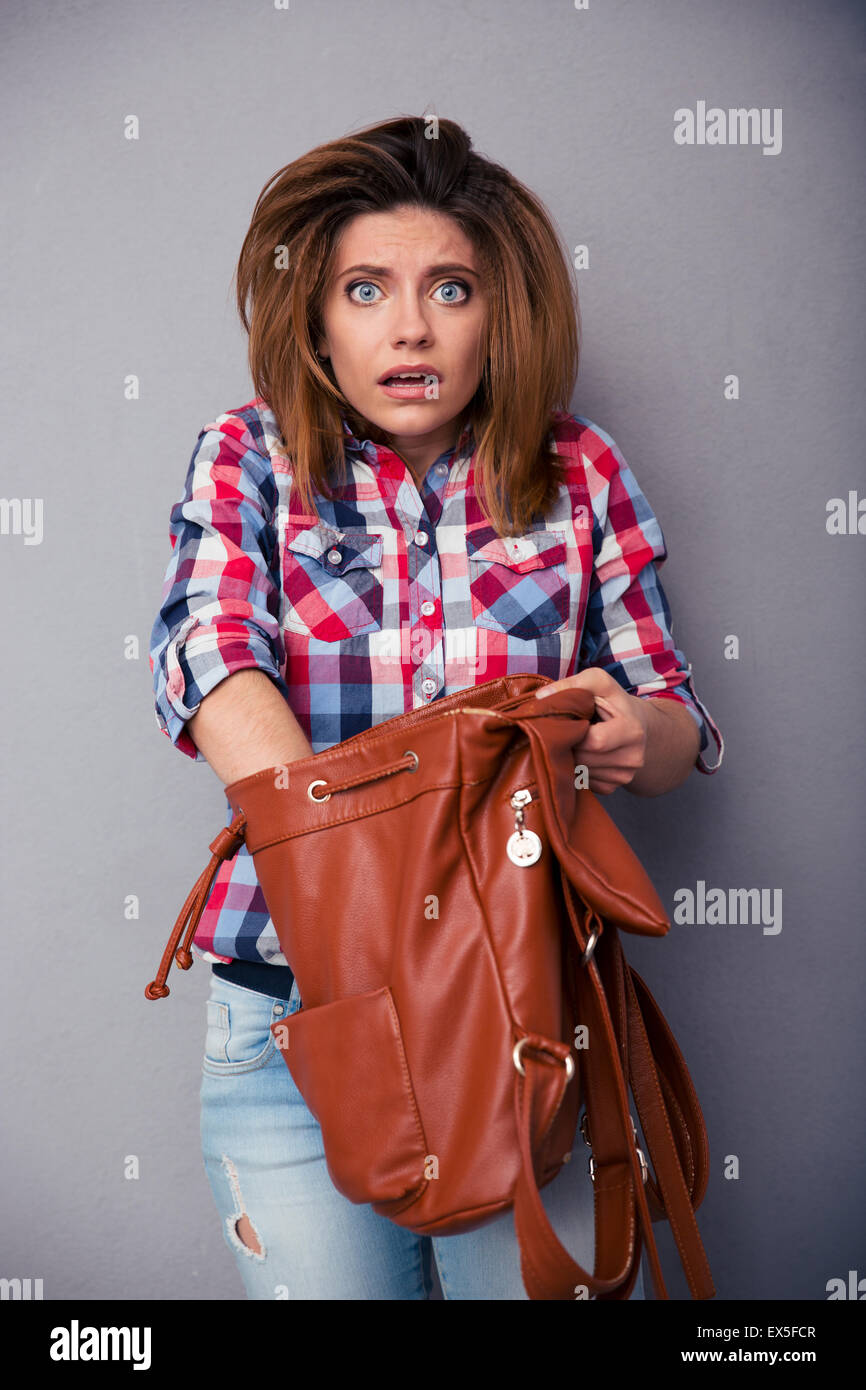 Confused woman searching something in her bag over gray background and looking at camera - Stock Image