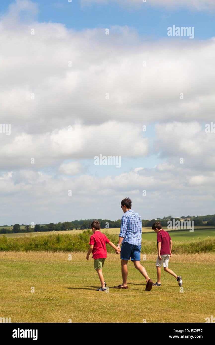 Man and two boys enjoying the countryside at Old Sarum, near Salisbury, Wiltshire in July - Stock Image