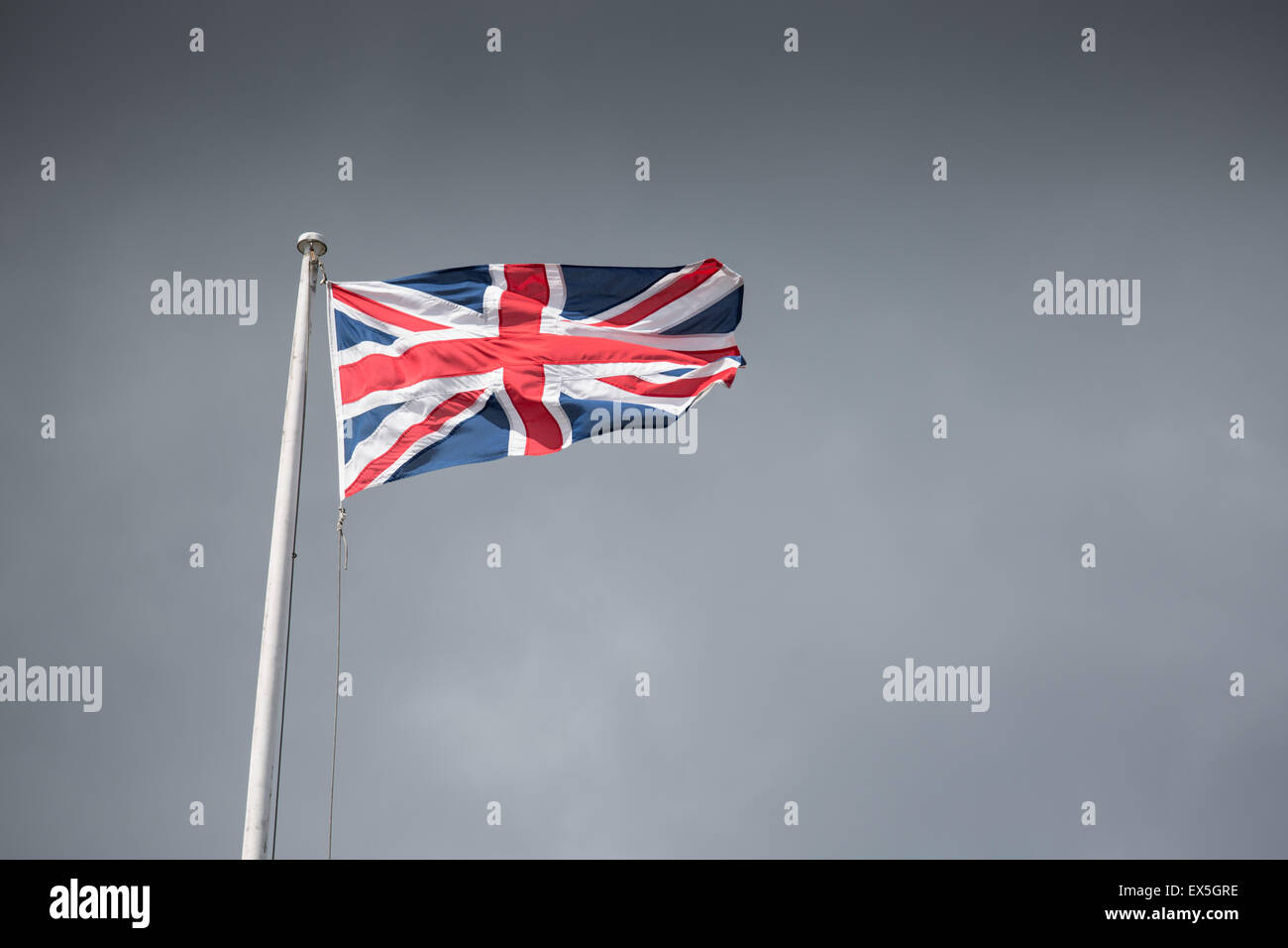 Union jack flag billowing against a dramatic sky Stock Photo