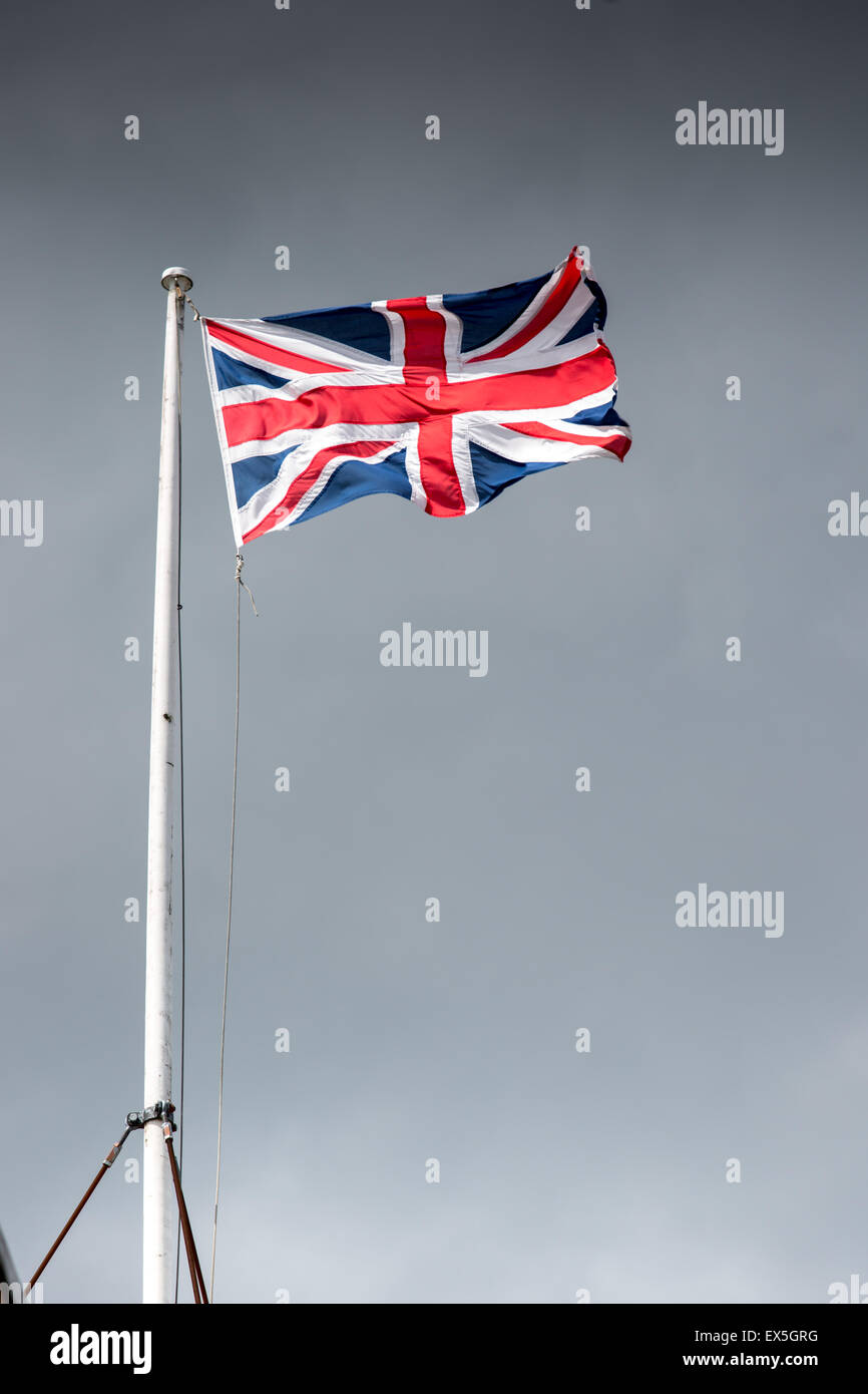 Union jack flag billowing against a dramatic sky - Stock Image