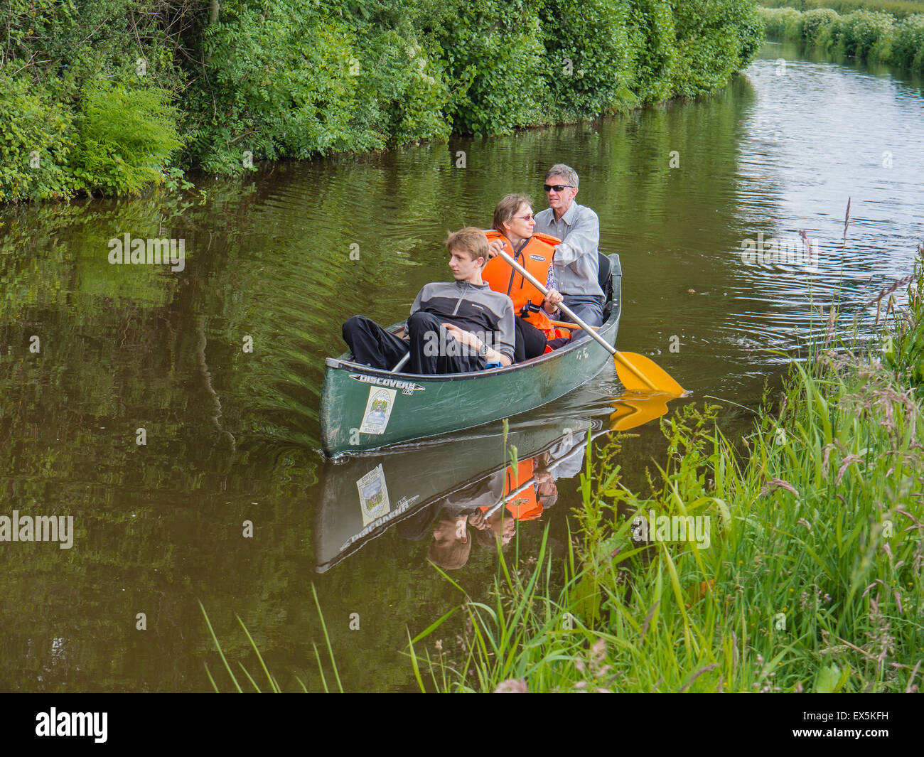 A family of three enjoy a canoe trip on the Monmouthshire and Brecon Canal, (Mon & Brec), near Brecon, Powys, - Stock Image
