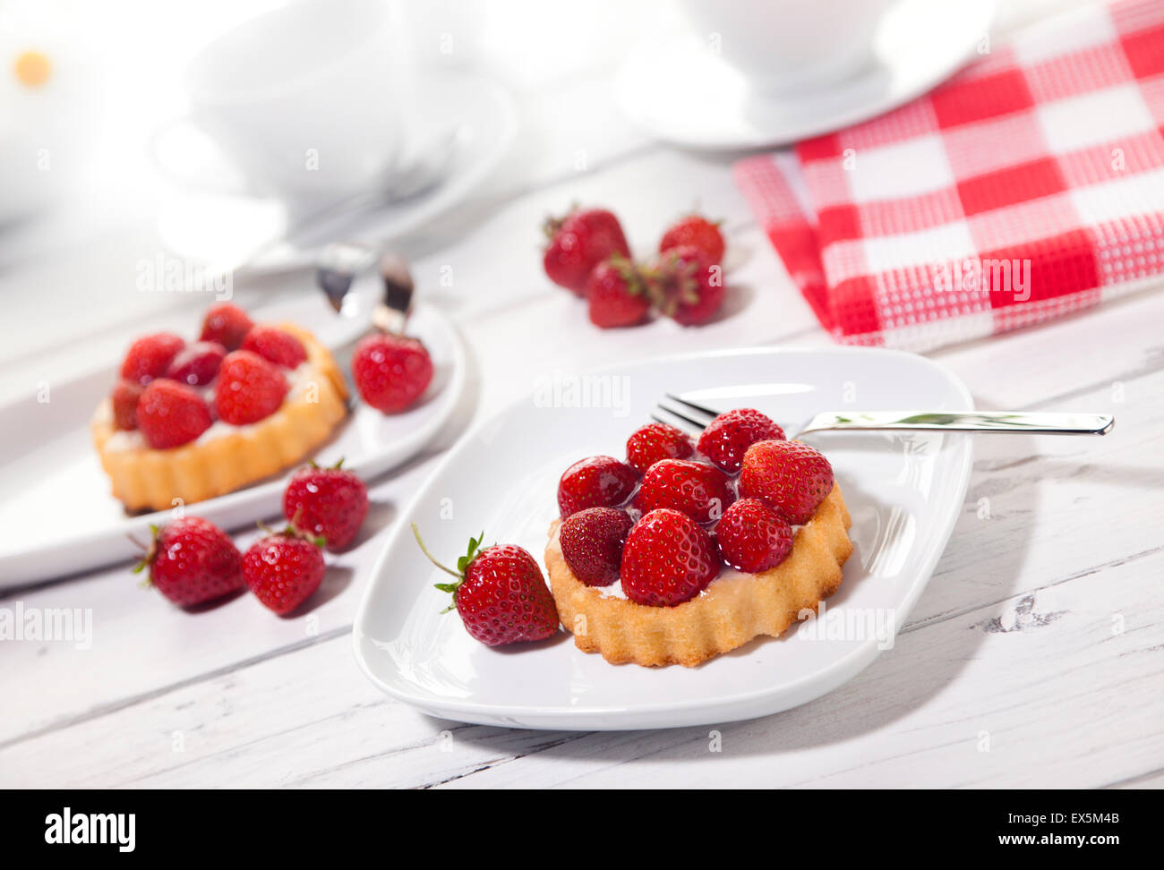 Strawberry shortcakes on coffee table, tilted view - Stock Image