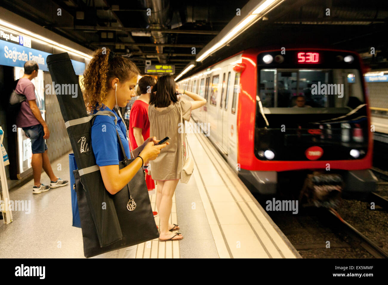 A young woman waiting for a train on the station platform at Sagrada Familia,  the Barcelona Metro, Barcelona, Spain - Stock Image