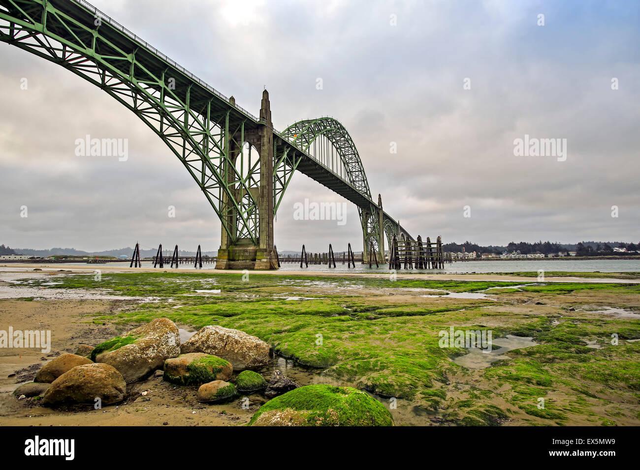 Rocks, moss and Yaquina Bay Bridge, Newport, Oregon USA - Stock Image