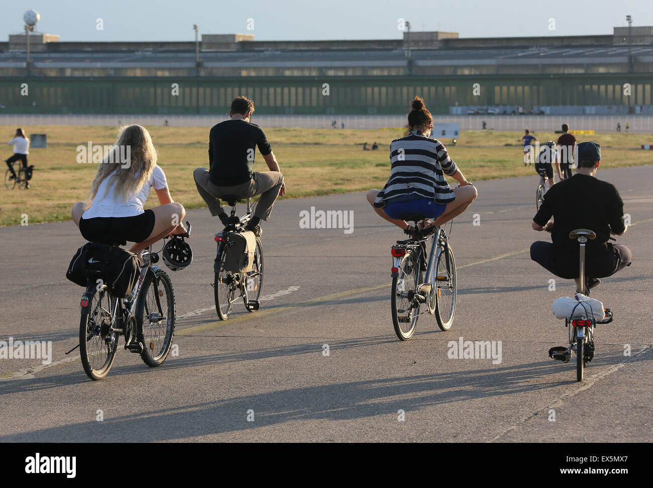 Participants of a YogaCycling course excercise on the Tempelhofer Feld in Berlin, Germany, 11 June 2015. YogaCycling - Stock Image