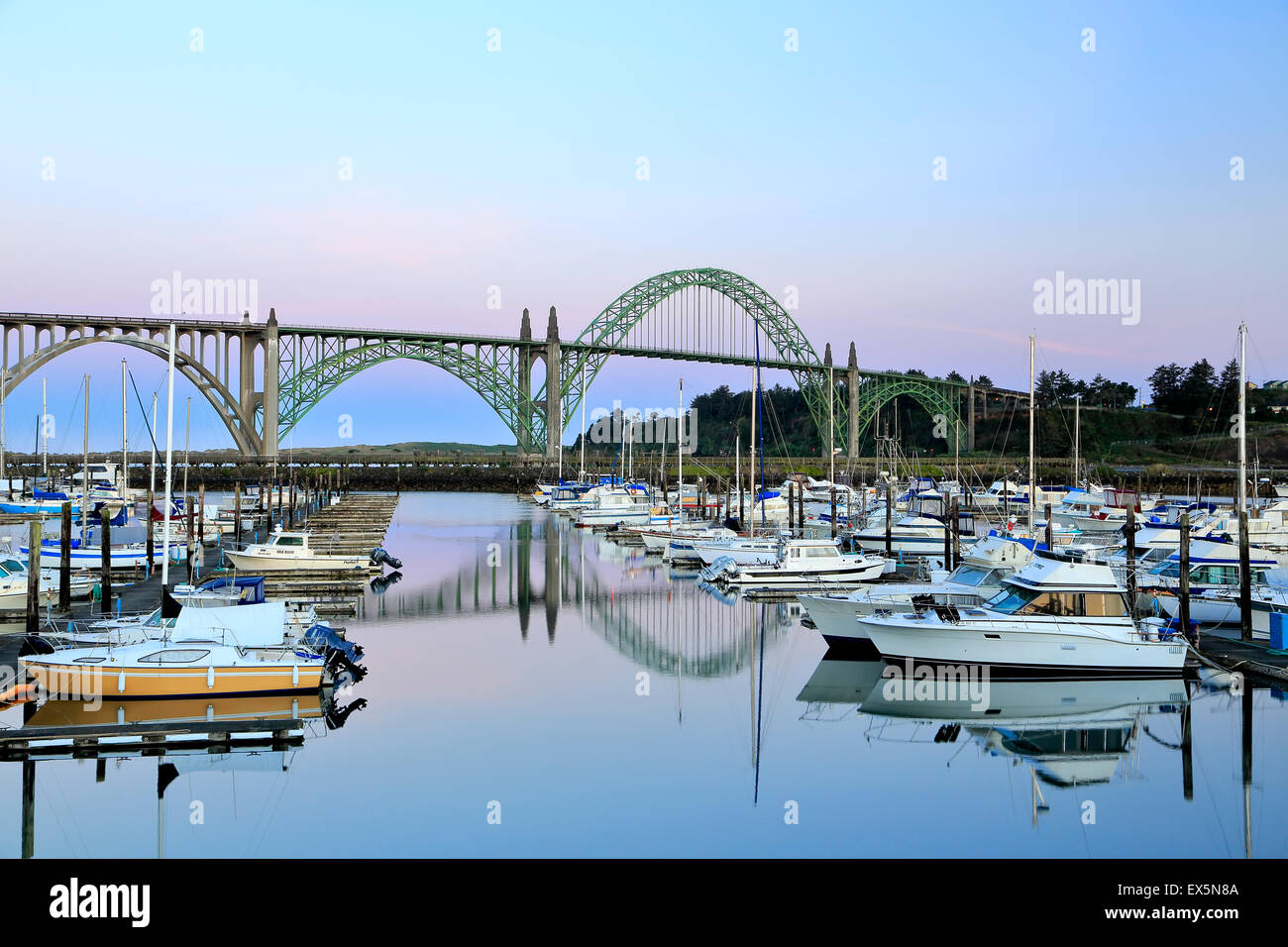 Boats moored in Port of Newport Marina and Yaquina Bay Bridge, Newport, Oregon USA Stock Photo