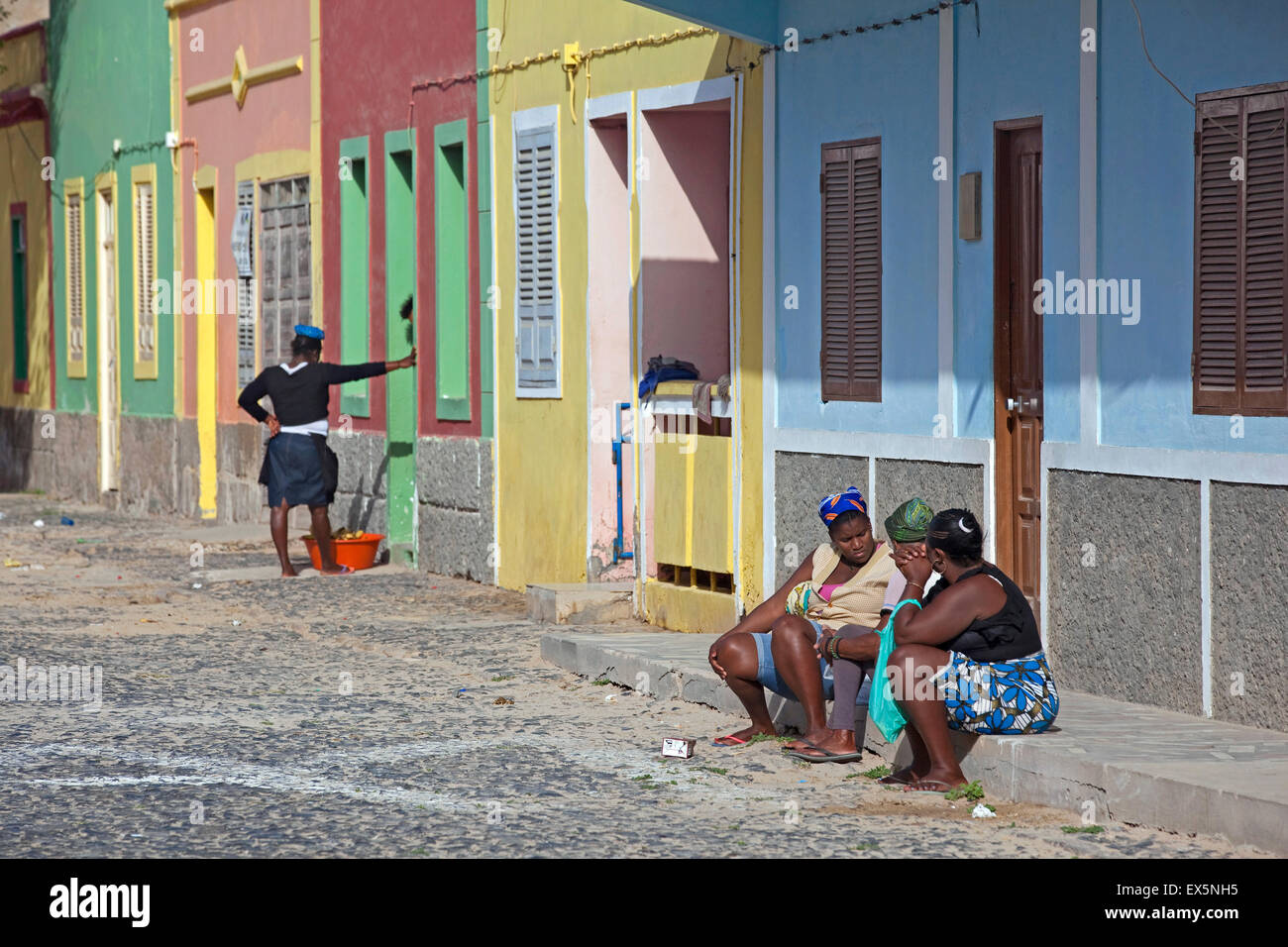 Creole women talking on doorstep in street in the village Sal Rei on the island Boa Vista, Cape Verde / Cabo Verde, - Stock Image