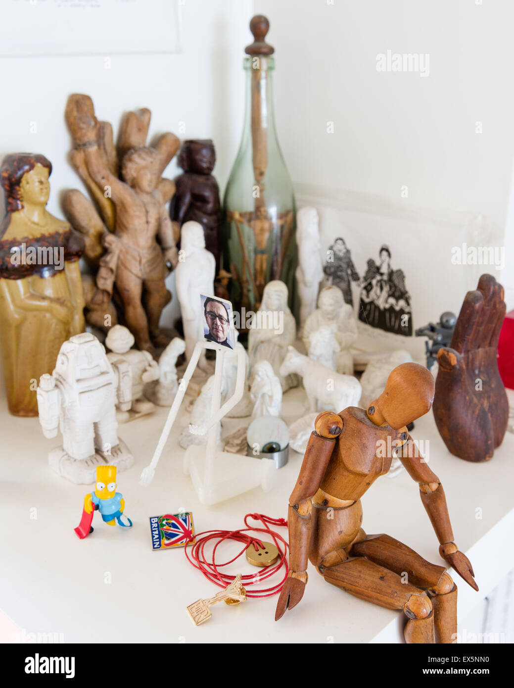 Artists wooden mannequin surrounded by small sculpted figurines - Stock Image