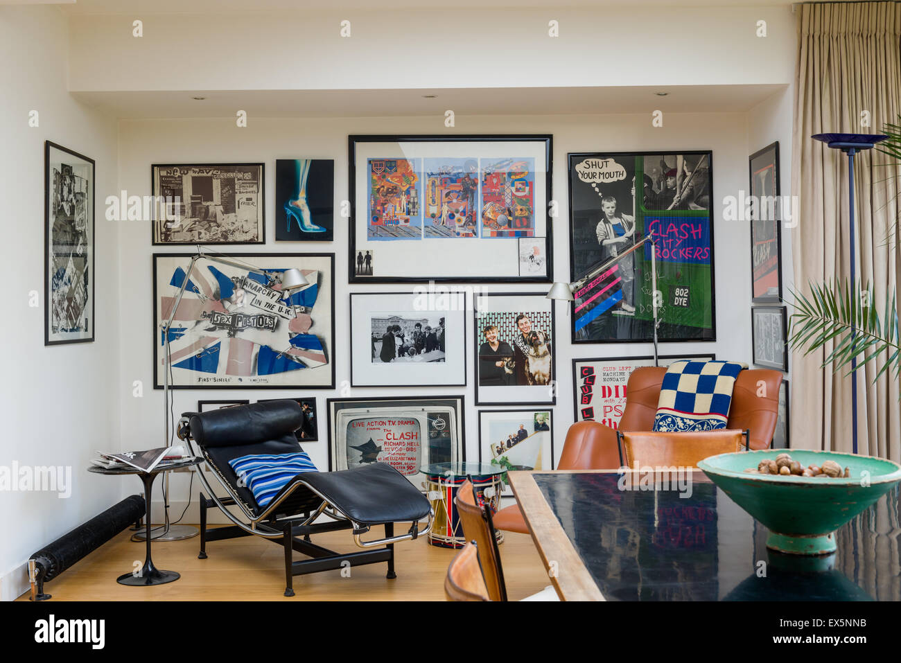 A variety of Clash related art work adorns a wall in a sitting room with Corbusier-style chairs - Stock Image