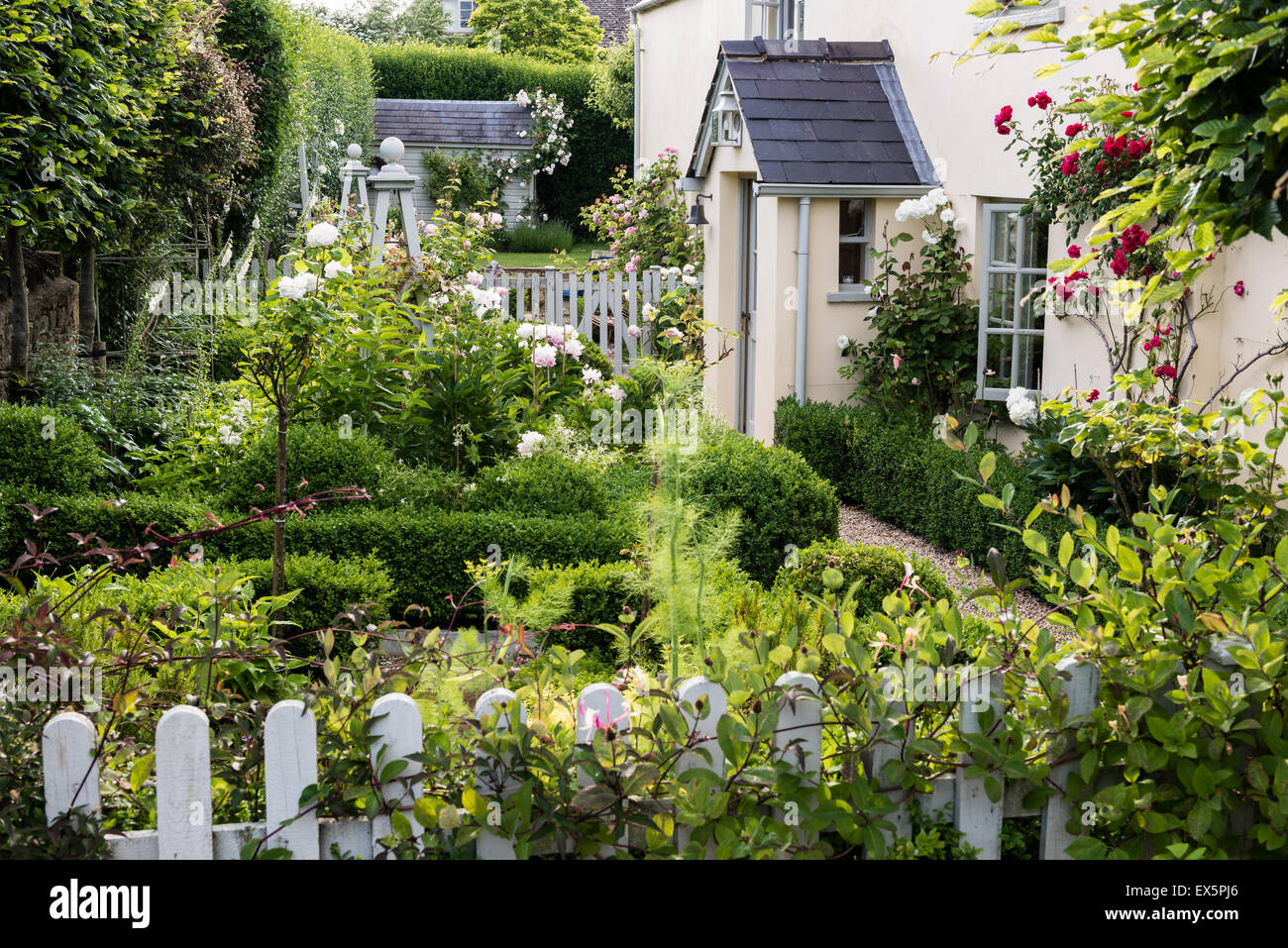 Exterior Facade Of An English Country Cottage With Picket Fence And Rose Garden