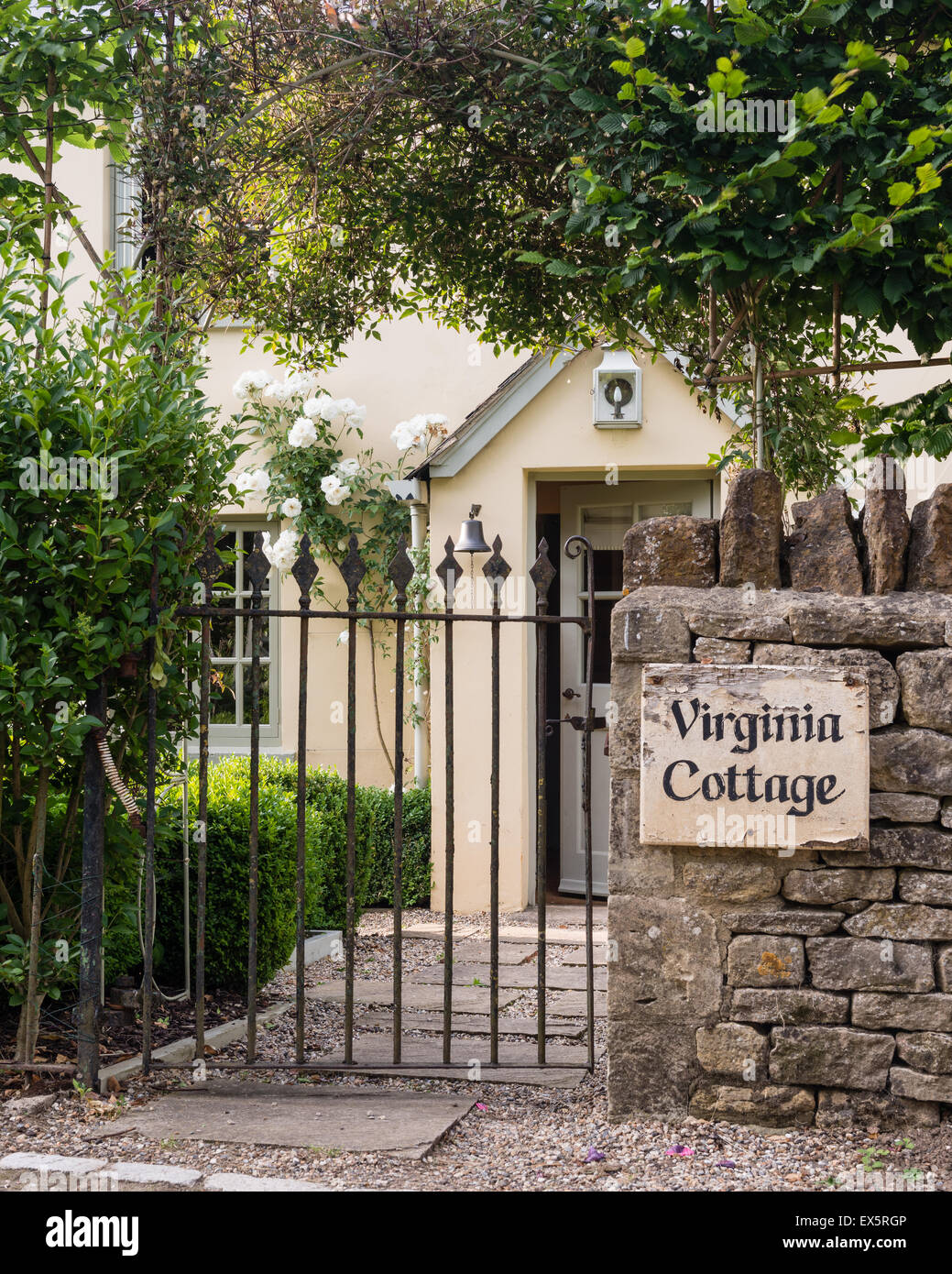 Wrought iron gate entrance to English country cottage - Stock Image