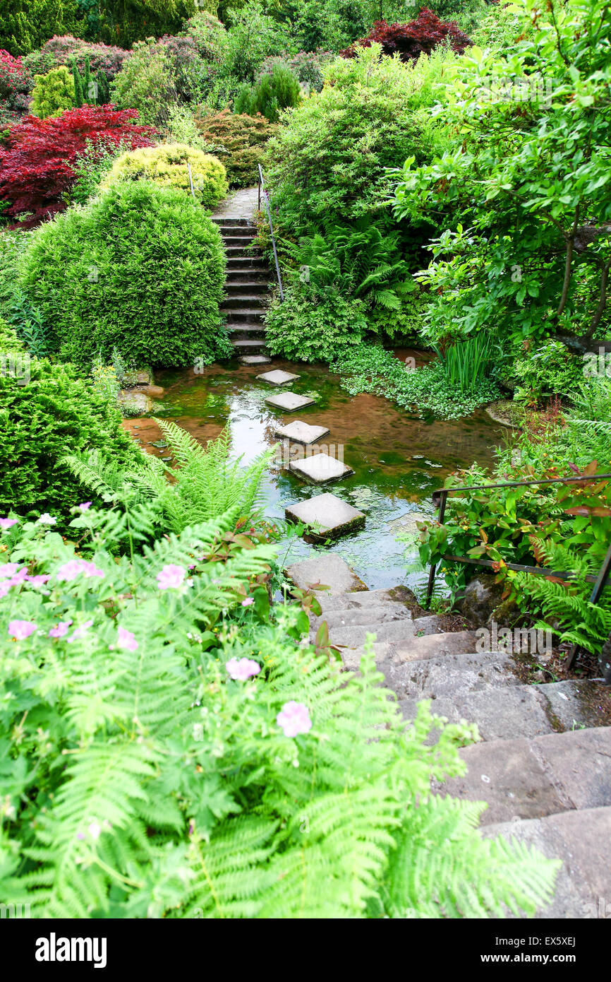 Steps and stepping stones leading across a stream at Alton Towers Estate Theme Park Gardens Staffordshire England UK Stock Photo