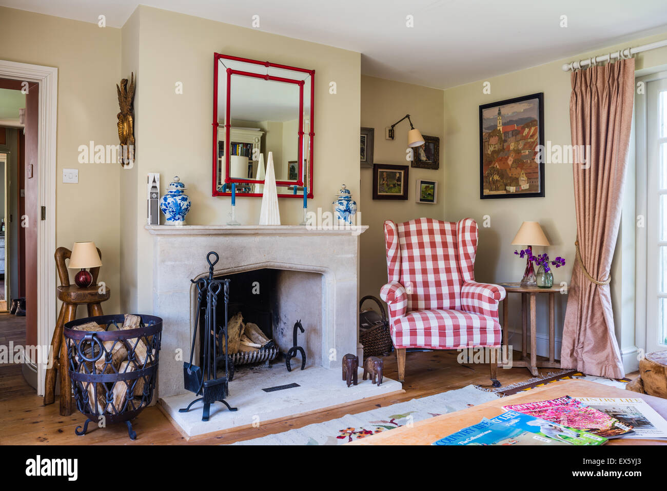 Gingham wingback chair in sitting room with stone fireplace and Murano glass mirror - Stock Image