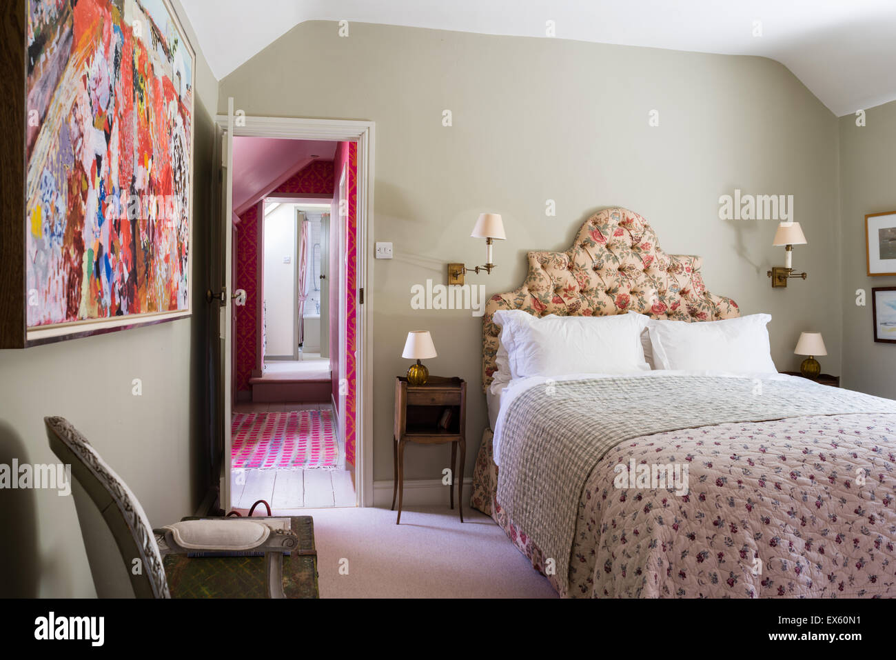 Mounted fabric print on wall of cottage bedroom with quilted throw and Bennison's Shangri-la fabric curtains - Stock Image