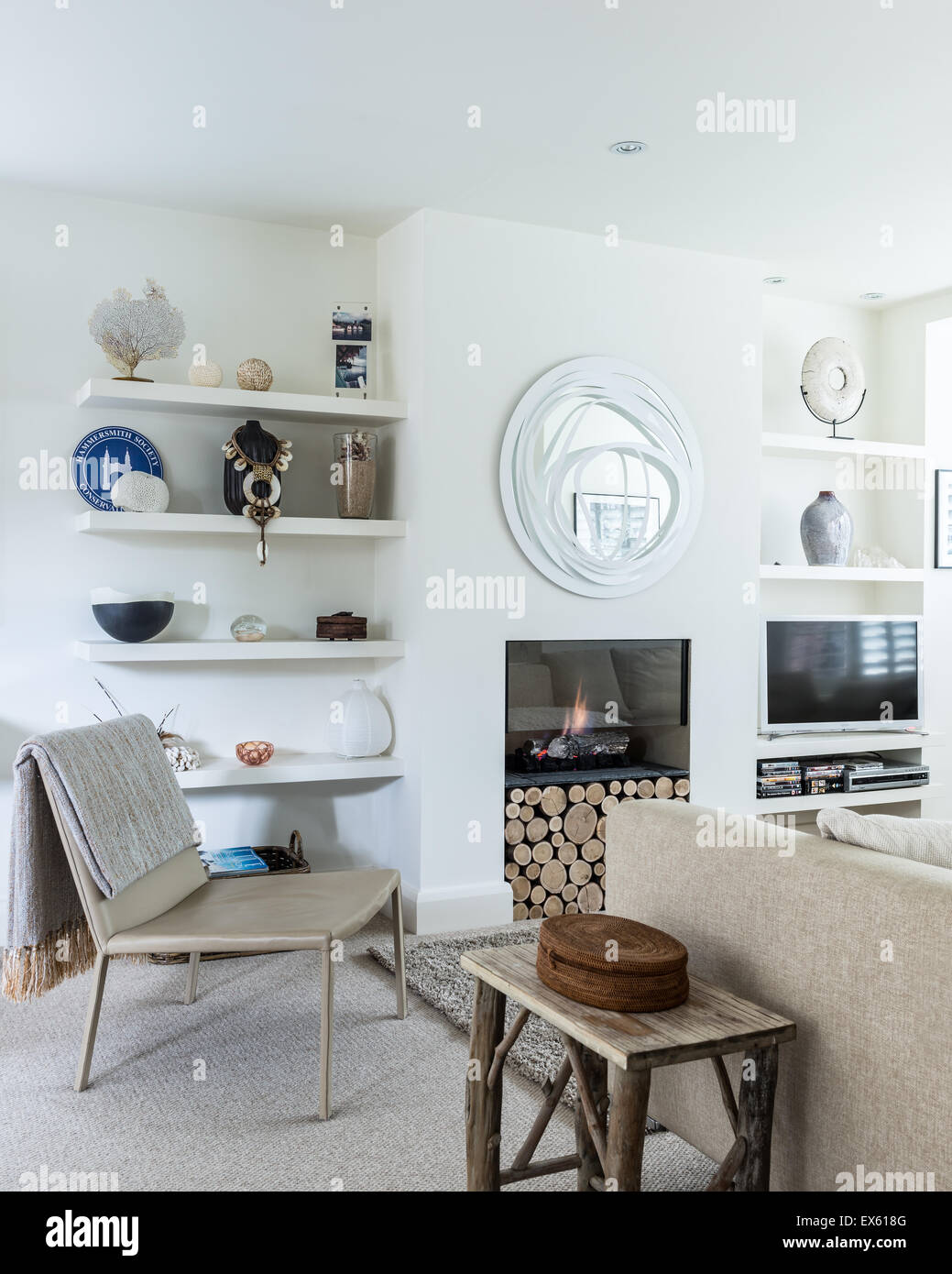 White sitting room with oatmeal carpet and Nu-Flame fireplace. The mirror above is by Constanze Scheweda - Stock Image
