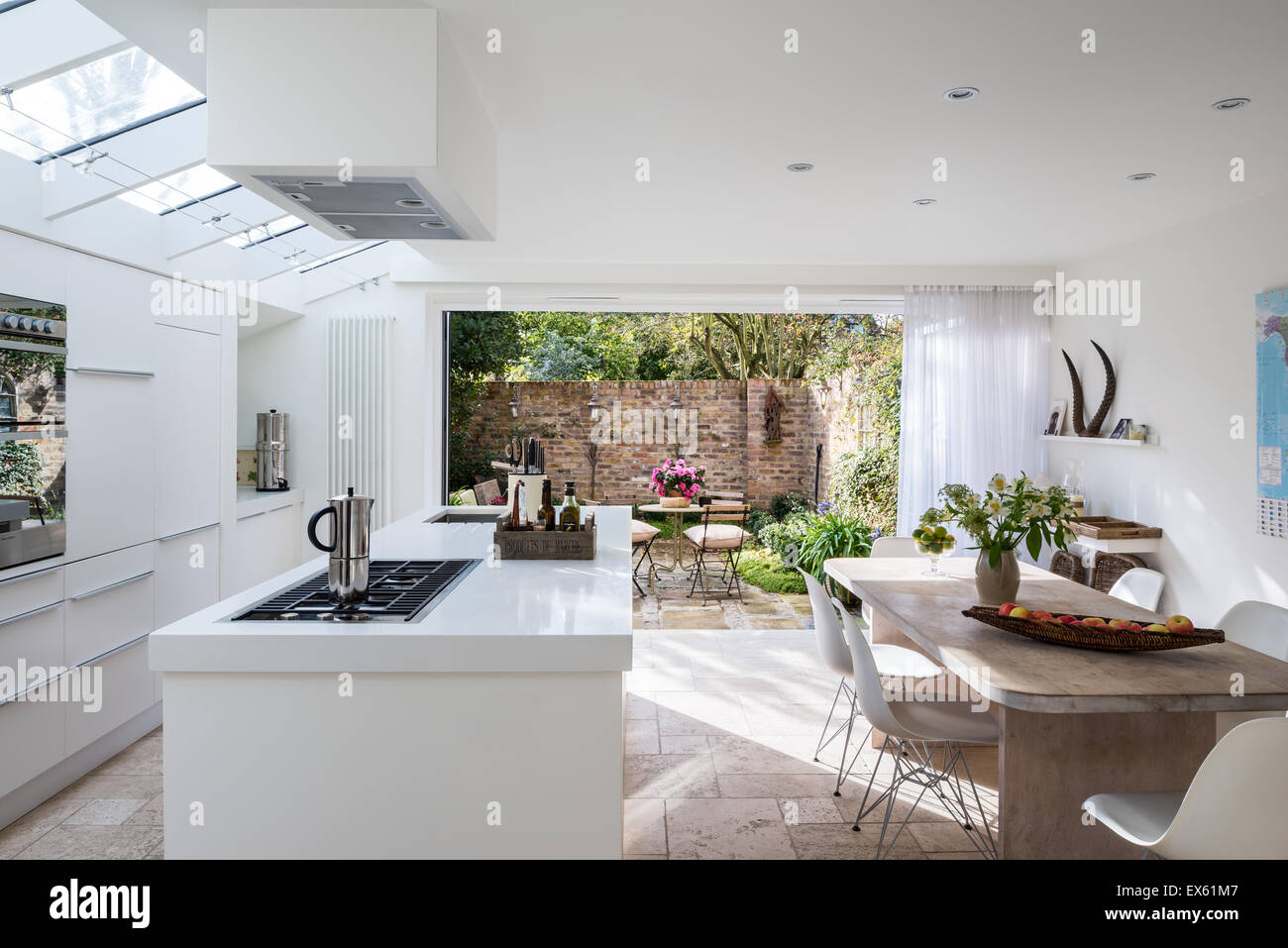 Open plan white modern kitchen with custom made table of lime and ...