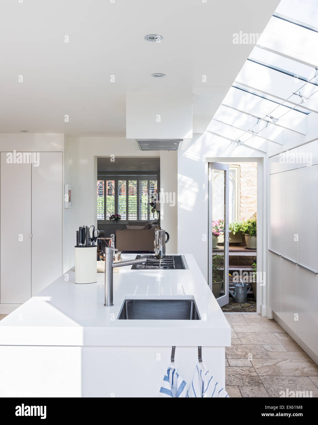 Open plan white modern kitchen with taps by Nu-Line. - Stock Image