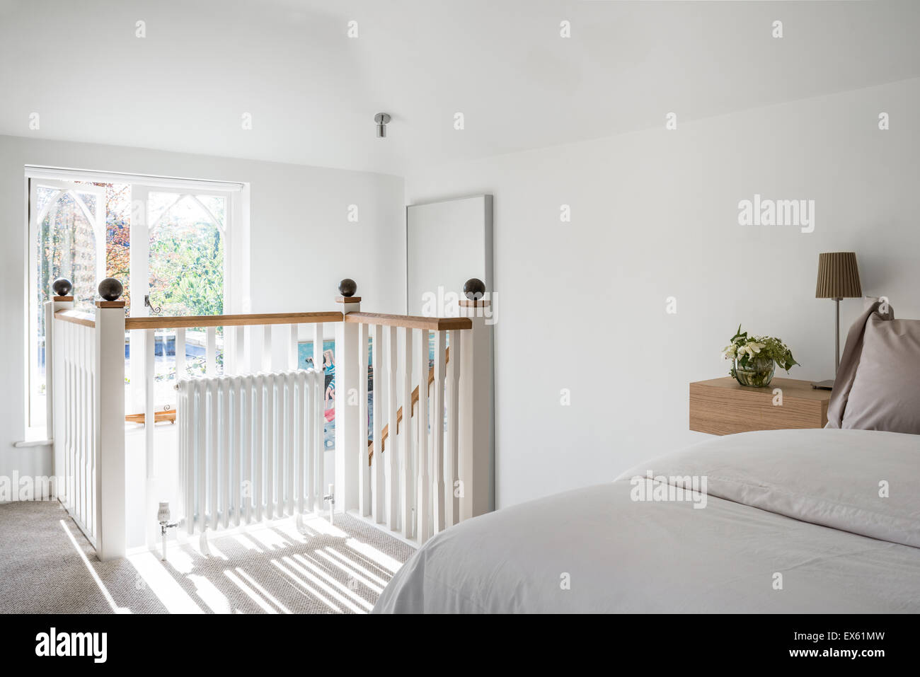 Loft style white bedroom with simple lamps from Ikea - Stock Image