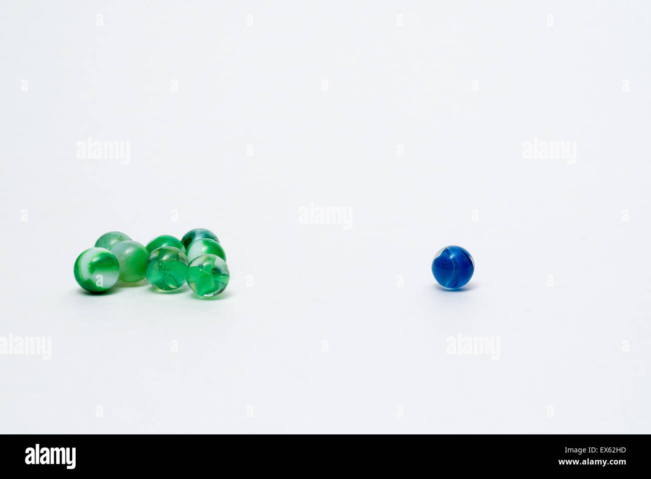 Group of Green Marbles Single Blue Marble, Blue Marble Alone, Singled Out Stock Photo