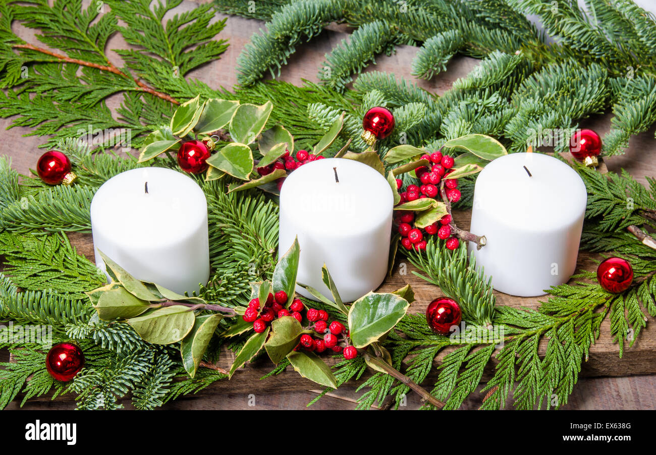 An Evergreen Christmas.An Evergreen Christmas Centerpiece With Three White Candles