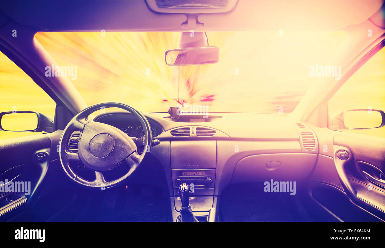 Vintage retro toned picture of a car interior at sunset. Stock Photo