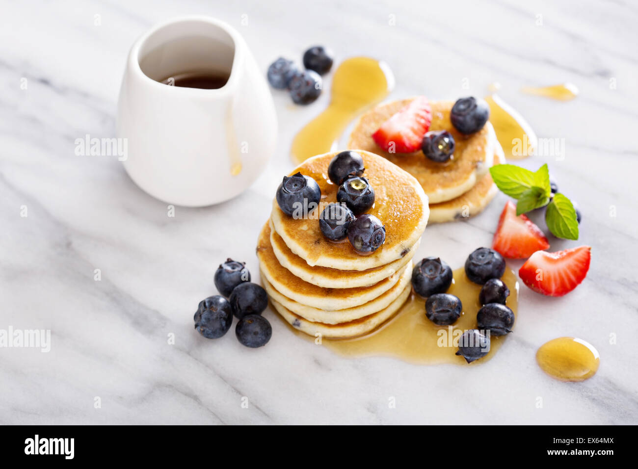 Stack of small pancakes with berries on marble board - Stock Image