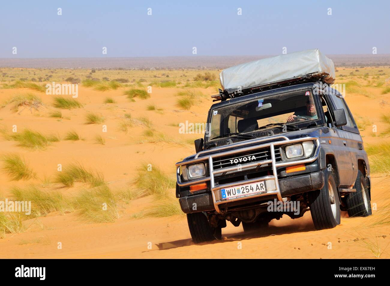 SUV with roof tent on the road in the desert, route from Atar to Tidjikja, Adrar region, Mauritania - Stock Image