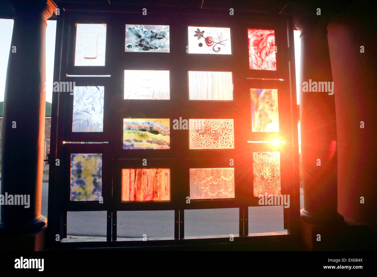 Ambient sunset light passing through stain glass windows - Stock Image