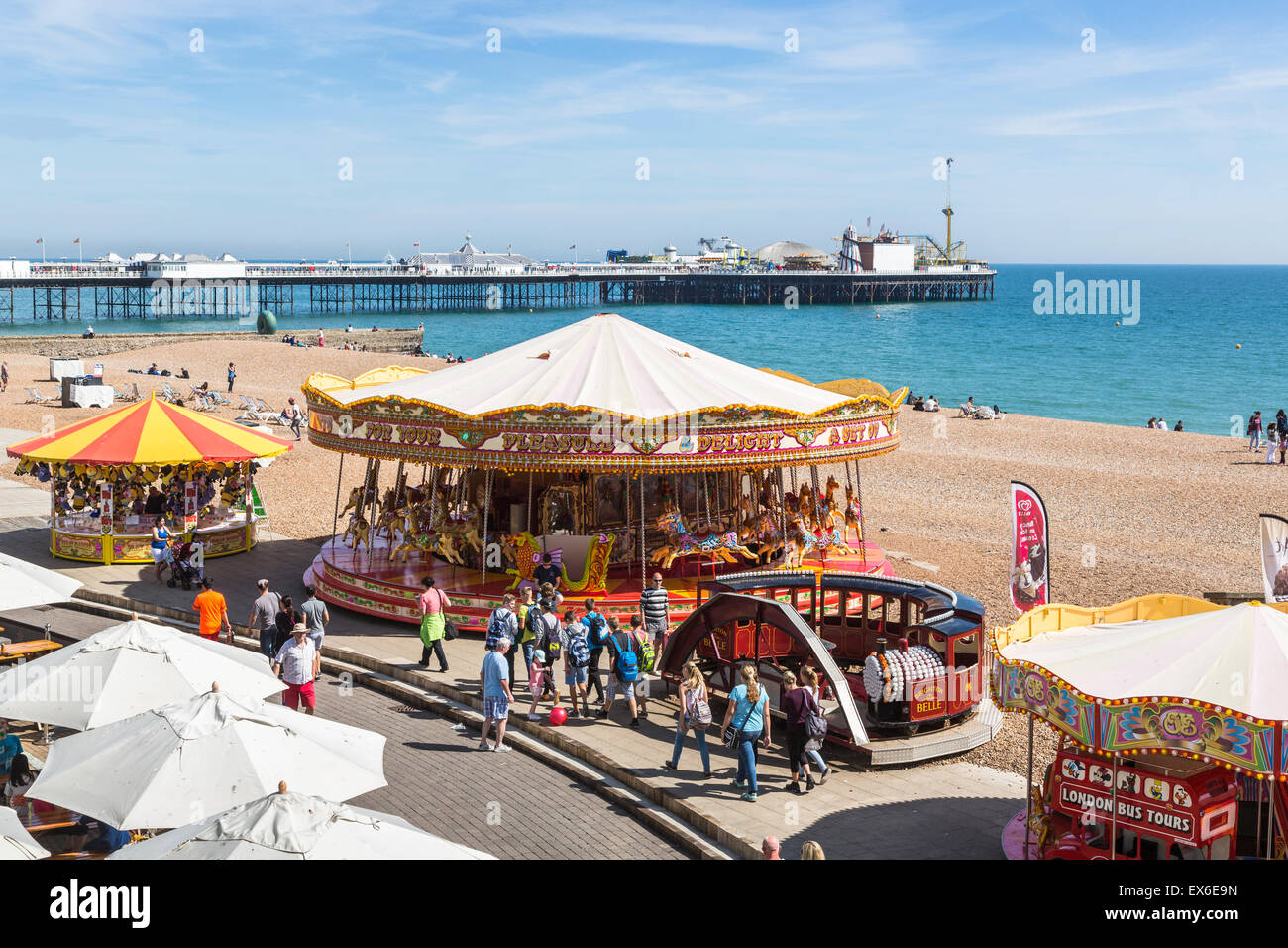 Seafront merry-go-round and funfair stalls on the beach on a sunny summer's day in Brighton, East Sussex, UK - Stock Image
