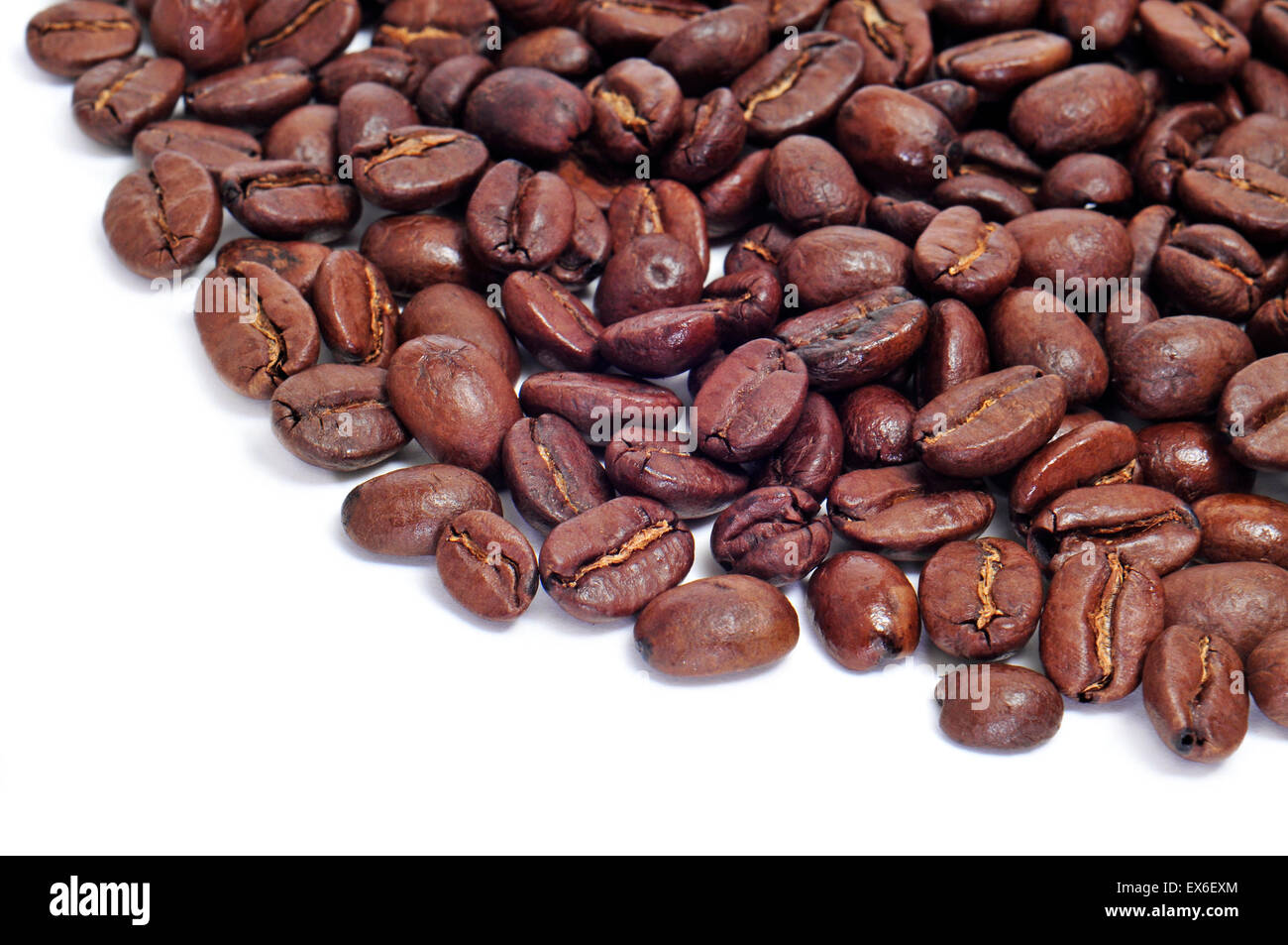 a pile of roasted coffee beans on a white background - Stock Image