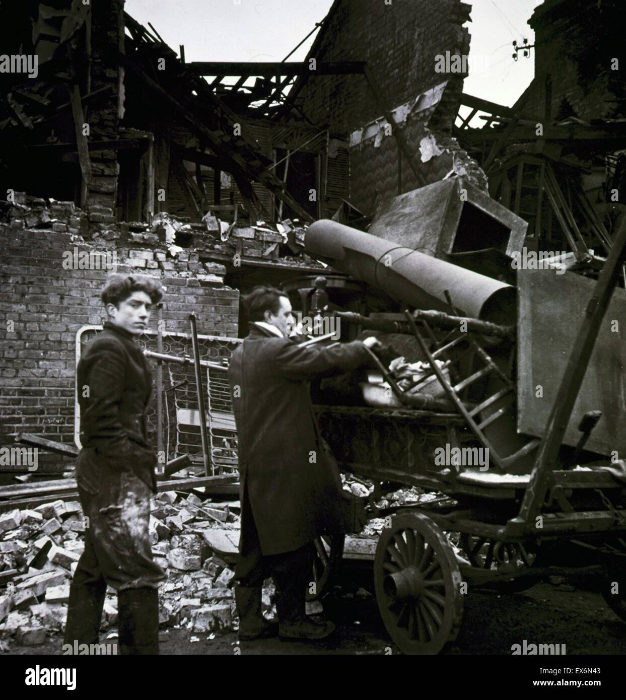 Photograph of two men loading their possessions after the Battersea Bombing Incident amongst ruins. Dated 1945 - Stock Image
