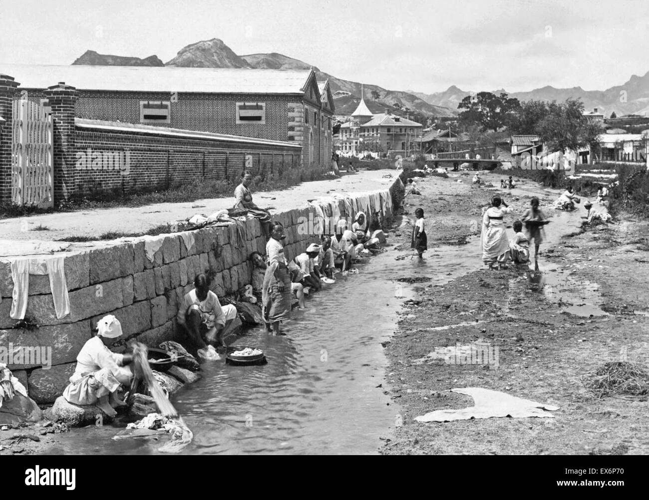 India under the British raj. Women are shown washing laundry in the stream running through a side street, ca. 1904 - Stock Image